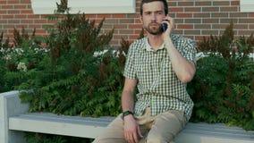 L'homme habillé occasionnel s'asseyent sur le banc et parler à un téléphone portable banque de vidéos