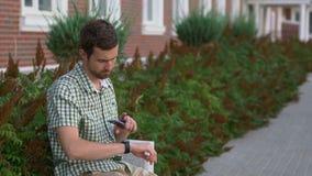 L'homme habillé occasionnel s'asseyent sur le banc et utilisent son smartwatch et smartphone clips vidéos