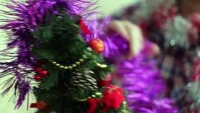 L'homme habille le beau petit arbre de Noël rougeoyant banque de vidéos