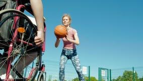 L'homme handicapé joue au basket-ball de son fauteuil roulant avec une femme, sur l'air ouvert, font un effort en jouant Photographie stock libre de droits