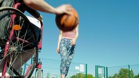 L'homme handicapé joue au basket-ball de son fauteuil roulant avec une femme, sur l'air ouvert, font un effort en jouant Images libres de droits