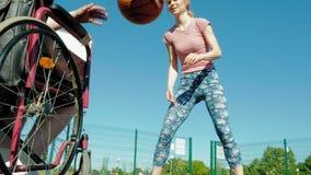 L'homme handicapé joue au basket-ball de son fauteuil roulant avec une femme, sur l'air ouvert, font un effort en jouant Photo stock
