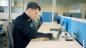 L'homme handicapé s'assied à une table avec un ordinateur portable, vue de côté banque de vidéos