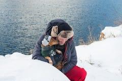 L'homme heureux étreint le petit chien, portant dans un chapeau drôle d'hiver Images libres de droits