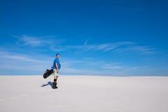 L'homme heureux avec un surf des neiges dans des mains se tient dedans sur la dune de sable Photos libres de droits