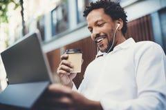 L'homme heureux d'Afro-américain dans des écouteurs faisant l'appel visuel par l'intermédiaire du pavé tactile électronique avec  Photo libre de droits
