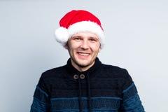 L'homme heureux de nouvelle année de Noël dans le chapeau de Santa Claus dépeint divers Photo stock