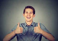 L'homme heureux donnant des pouces lèvent le signe Photos libres de droits