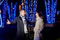 L'homme heureux et une femme marchant dans la soirée se garent Image libre de droits