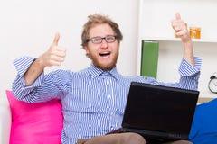 L'homme heureux montre le signe CORRECT devant un ordinateur Photos stock