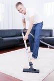 L'homme heureux nettoie dans la salle moderne avec le vide. photo stock