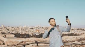 L'homme heureux prend le selfie dans la vieille ville Jérusalem Le mâle local barbu sourit heureux, prenant des photos Panorama p clips vidéos