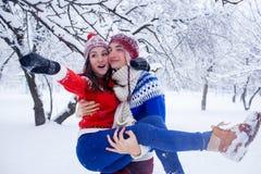 L'homme heureux tient son amie dans des ses bras dans la forêt d'hiver Photos stock