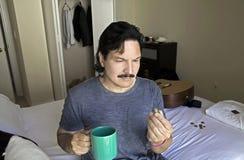 L'homme hispanique regarde la pilule d'huile de poisson avant de la prendre avec le bevera photo stock