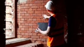 L'homme l'historien examine les murs du vieux bâtiment, vérifie la densité de la brique, préparation pour clips vidéos