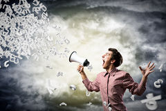 L'homme hurle dans un mégaphone Photographie stock libre de droits