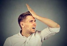 L'homme idiot, giflant la main sur la tête ayant duh le moment regrette images libres de droits