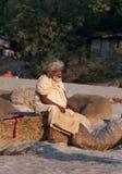 L'homme indien s'assied sur la roche à la plage près de la rivière Ganga Image libre de droits