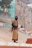 L'homme indien se tient sur les étapes du ghat près de la rivière sacrée le Gange à Varanasi Photos libres de droits