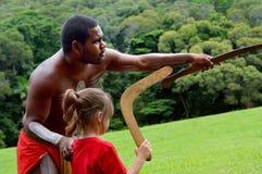 L'homme indigène d'Australiens enseigne à une jeune fille comment jeter un b image libre de droits