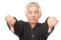 L'homme japonais supérieur avec des pouces font des gestes vers le bas Photographie stock
