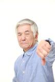 L'homme japonais supérieur avec des pouces font des gestes vers le bas Images stock