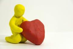 L'homme jaune de pâte à modeler de figurine s'assied sur ses genoux et tient le p Images stock