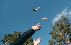 L'homme jetant ses chaussures rattrape son fond de ciel de mains photographie stock libre de droits