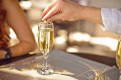 l'homme jette l'anneau de mariage en verre de champagne Photo stock