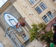 L'homme jette la boule dans l'anneau, concours de streetball sur Freedo Photo stock