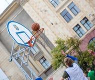 L'homme jette la boule dans l'anneau, concours de streetball sur Freedo Images stock