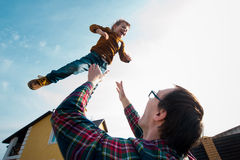 L'homme jette le garçon dans le ciel Photographie stock libre de droits