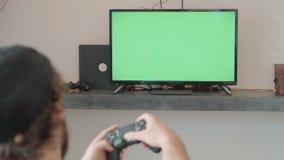 L'homme joue avec un emplacement whiile de contrôleur de jeu sur le divan à la maison banque de vidéos