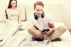 L'homme joue la femme de jeu d'ordinateur de playstation que l'amie est fâchée pour lui Photo libre de droits