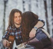 L'homme joue la guitare à son amie dans la forêt d'hiver Photo libre de droits