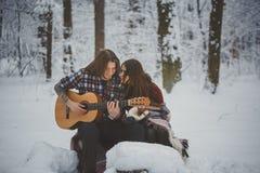 L'homme joue la guitare à son amie dans la forêt d'hiver Photos stock