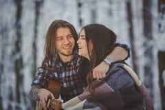 L'homme joue la guitare à son amie dans la forêt d'hiver Photo stock