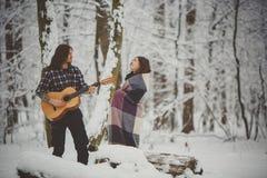 L'homme joue la guitare à son amie dans la forêt d'hiver Images stock