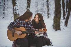 L'homme joue la guitare à son amie dans la forêt d'hiver Image libre de droits