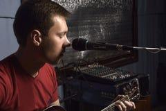 L'homme joue la guitare et chante Photographie stock
