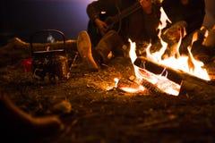 L'homme joue la guitare et la femme au sujet du feu sur le fond du ciel étoilé Images stock