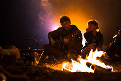 L'homme joue la guitare et la femme au sujet du feu sur le fond du ciel étoilé Photo libre de droits