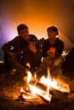 L'homme joue la guitare et la femme au sujet du feu sur le fond du ciel étoilé Photographie stock
