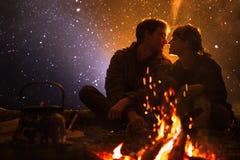 L'homme joue la guitare et la femme au sujet du feu sur le fond du ciel étoilé Images libres de droits