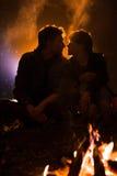 L'homme joue la guitare et la femme au sujet du feu sur le fond du ciel étoilé Photographie stock libre de droits