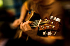 L'homme joue la guitare jouant la guitare de guitare et ficelle des cordes de guitare Photographie stock libre de droits