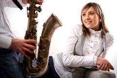 L'homme joue le saxophone pour la fille Image stock
