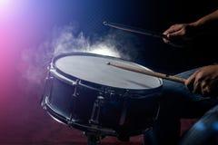 L'homme joue le tambour de piège à l'arrière-plan de faible luminosité Images libres de droits