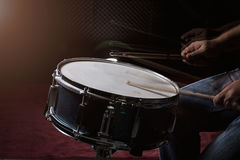 L'homme joue le tambour réglé à l'arrière-plan de faible luminosité Photographie stock libre de droits