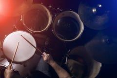 L'homme joue le tambour réglé à l'arrière-plan de faible luminosité Image libre de droits